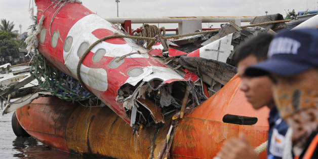 Security guards stand near the newly-recovered remains of the fuselage of the ill-fated AirAsia Flight 8501 on the deck of rescue ship Crest Onyx at Tanjung Priok port in Jakarta, Indonesia, Monday, March 2, 2015. The Airbus A320-200 with 162 people on board crashed into the Java Sea on Dec. 28, 2014 while flying from Surabaya, East Java, to Singapore. (AP Photo/Dita Alangkara)