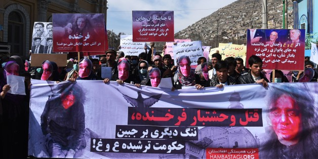 Afghan members of the Solidarity Party of Afghanistan wearing masks bearing an impression of the bloodied face of a woman who was lynched by a mob chant slogans during a protest against the attack in Kabul on March 23, 2015. Afghan woman who was beaten to death and set on fire by a mob for allegedly burning a copy of the Koran. The body of Farkhunda, 27, who was lynched on March 19 by an angry mob in central Kabul, was carried to the graveyard by women amid crowds of men, an AFP reporter said, a rare act of protest in a male-dominated society. AFP PHOTO / SHAH Marai        (Photo credit should read SHAH MARAI/AFP/Getty Images)