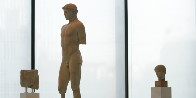 A 2,600-year-old marble statue of a youth is displayed in the new Acropolis Museum in Athens, Greece, on Wednesday, June 17, 2008. Greece's Orthodox Church on Wednesday formally blessed the new museum, which is scheduled to open this weekend. Greek officials hope one day to display the British Museum's Elgin Marbles from the Acropolis in the glass and concrete museum _ despite repeated refusals from London.(AP Photo/Petros Giannakouris)