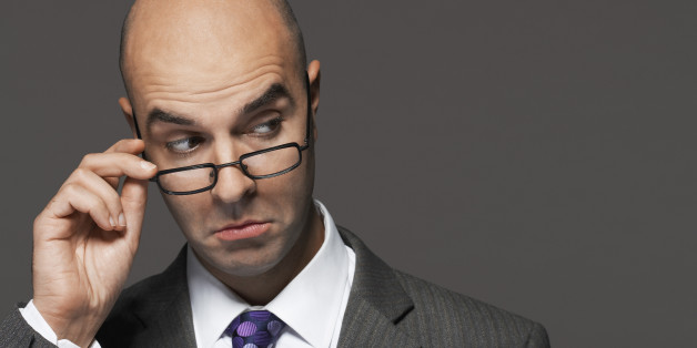 Closeup of a businessman with hand on glasses making a face against gray background