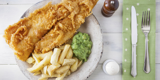 Traditional english food - Fish and chips with mushy peas on a white wooden background
