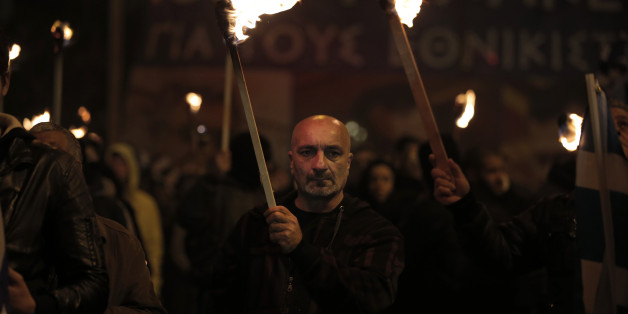 Supporters of Greece's extreme right party Golden Dawn, hold torches during a rally to commemorate a 1996 incident which cost the lives of three Greek navy officers and brought Greece and Turkey to the brink of war, in central Athens, Saturday, Jan. 31, 2015. The extreme right, anti-immigrant Golden Dawn party, which has Nazi roots, received the third-place in Sunday, Jan. 25's election. Its showing comes despite the fact that the party's leader and most of its lawmakers are behind bars, facing