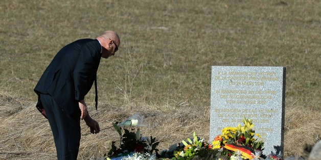 A man lays flowers at a memorial for the victims of the Germanwings plane crash in Le Vernet on March 27, 2015. The Germanwings co-pilot who crashed his Airbus into the French Alps, killing all 150 aboard, hid a serious illness from the airline, prosecutors said amid reports he was severely depressed. AFP PHOTO / BORIS HORVAT        (Photo credit should read BORIS HORVAT/AFP/Getty Images)