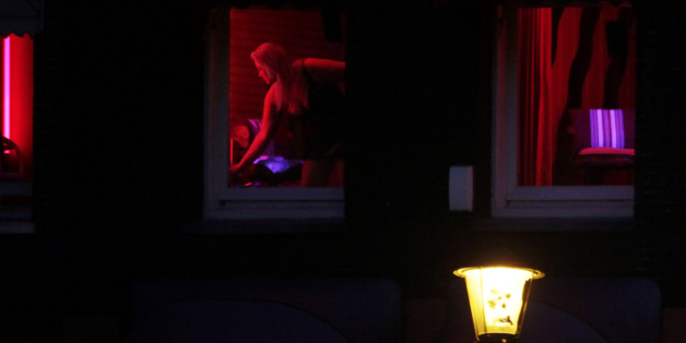 In this photo taken Monday Jan. 10, 2011 a prostitute advertises her wares behind red-lit windows in Amsterdam, Netherlands. Workers in the world's oldest profession are about to get a lesson in the harsh reality of Europe's new age of austerity. Amid budget cuts and falling revenues, the Dutch government has warned prostitutes who advertise their wares in the famed windows of Amsterdam's red light district to expect a business-only visit from the taxman this year. In a sign of the times, the move is meeting with little formal opposition, even among prostitutes, though some are skeptical it can be enforced. (AP Photo/Peter Dejong)