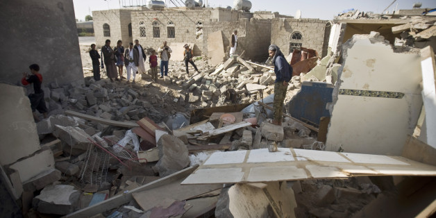 Yemenis gather near the rubble of houses destroyed by Saudi airstrikes near the airport in Sanaa, Yemen, Tuesday, March 31, 2015. (AP Photo/Hani Mohammed)