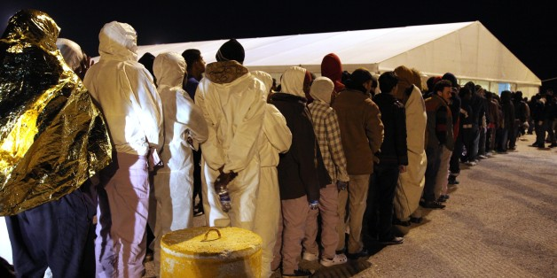 Rescued migrants line up after disembarking from an Italian Coast Guard ship in the harbor of Augusta, Sicily, southern Italy, Wednesday, March 4, 2015. In a dramatic sea rescue north of Libya, a flotilla of rescue ships saved nearly 1,000 migrants and refugees, while 10 migrants perished in the southern Mediterranean, Italian officials said Wednesday. The rescue vessels, including from Italy's coast guard and navy, and three cargo ships, saved 941 people in seven separate operations that began