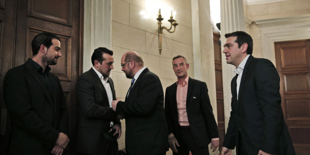 Greek Prime Minister Alexis Tsipras, right, looks on as European Parliament President Martin Schulz, center, shakes hands and talks with Greek Minister of State Nikos Pappas, second left, following a news conference after their meeting at Maximos Mansion in Athens, Thursday, Jan. 29, 2015. Schulz is the first European Union official to meet Tsipras, whose new Cabinet alarmed the Greek stock market Wednesday with promises to renege on a series of key budget commitments made by previous administra