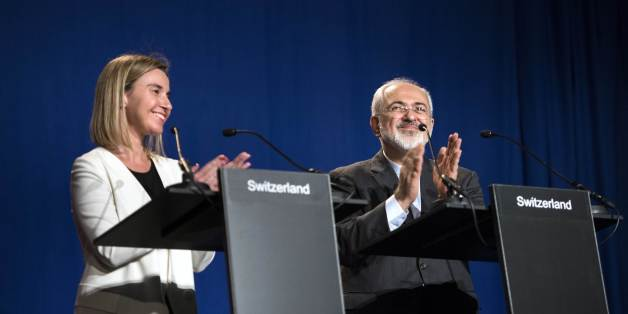 Iranian Foreign Minister Javad Zarif, right, claps with European Union High Representative for Foreign Affairs and Security Policy Federica Mogherini, after making a statement at the Swiss Federal Institute of Technology, or Ecole Polytechnique Federale De Lausanne,  in Lausanne, Switzerland, Thursday, April 2, 2015, after Iran nuclear program talks finished with extended sessions. The United States, Iran and five other world powers on Thursday announced an understanding outlining limits on Iran