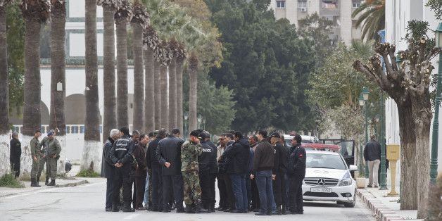 Tunisian police and defense officials gather outside the National Bardo museum in Tunis, Tunisia, Saturday March 21, 2015. The two extremist gunmen who killed 21 people at a museum in Tunis trained in neighboring Libya before caring out the deadly attack, a top Tunisian security official said. (AP Photo/Michel Euler)