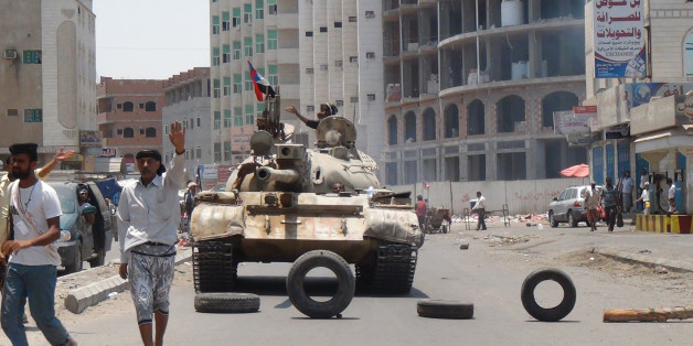 Militiamen loyal to Yemen's President Abed Rabbo Mansour Hadi take positions at a street in Aden, Yemen, Thursday, April 2, 2015. Yemen's Shiite rebels and their allies fought their way through the commercial center of Aden on Thursday and seized the presidential palace on a strategic hilltop in this southern coastal city, security officials said. (AP Photo/Wael Qubady)