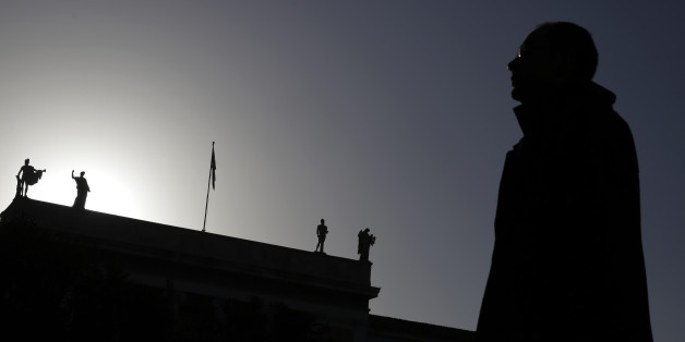 A pedestrian walks past statues, which stand at the top of the National Archaeological Museum of Greece in central Athens, on Thursday, Feb. 26, 2015. Greece's prime minister Alexis Tsipras held a marathon meeting with his party's lawmakers Wednesday, briefing them on pledges made to European creditors to win a four-month extension of the country's bailout amid simmering party discontent over what some see as a capitulation. The meeting, which was held behind closed doors, lasted more than 11 hours. (AP Photo/Petros Giannakouris)