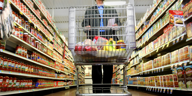 A man pushes his cart down a grocery aisle while shopping for groceries.