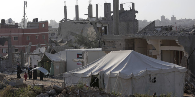 Palestinian women stand in front of a tent they set up next to their destroyed house in the Shijaiyah neighborhood of Gaza City, Monday, March 30, 2015. Despondent over the slow pace of post-war reconstruction, displaced Gazans have begun to return to their damaged homes, patching up the structures with blankets and plastic sheets and living in the unstable and unsafe structures while they wait for promised aid to arrive. (AP Photo/Khalil Hamra)