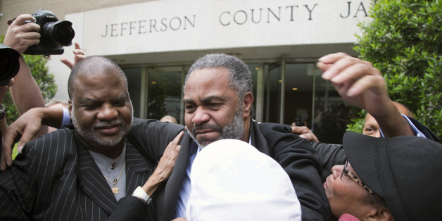 Friend Lester Bailey, left, and others greet Anthony Ray Hinton, center, as Hinton leaves the Jefferson County jail, Friday, April 3, 2015, in Birmingham, Ala. Hinton spent nearly 30 years on Alabama's death row, and was set free Friday after prosecutors told a judge they won't re-try him for the 1985 slayings of two fast-food managers. (AP Photo/ Hal Yeager)