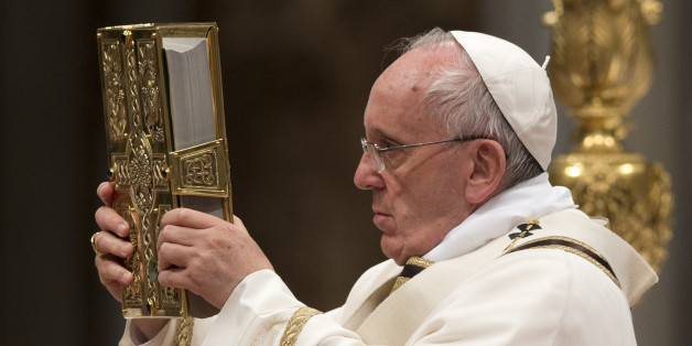 Pope Francis holds the Holy Book as he celebrates an Easter vigil service, in St. Peter's Basilica, at the Vatican, Saturday, April 4, 2015. (AP Photo/Andrew Medichini)