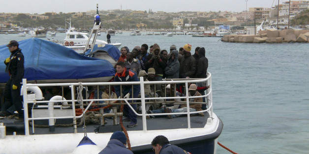 An Italian Coast Guard boat carrying some would-be immigrants, rescued at sea, reaches the port of the tiny Italian island of Lampedusa in this March 29, 2009 photo made available Tuesday, March 31, 2009.  Vessels carrying hundreds of migrants capsized off the coast of Libya in separate incidents over the last two days and more than 300 people were believed to have drowned, an international migration group said Tuesday. (AP Photo)