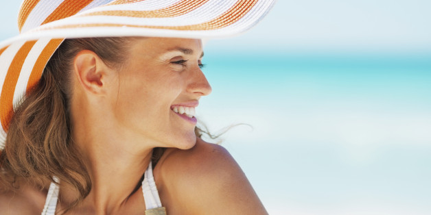 Portrait of happy young woman in swimsuit and beach hat looking on copy space