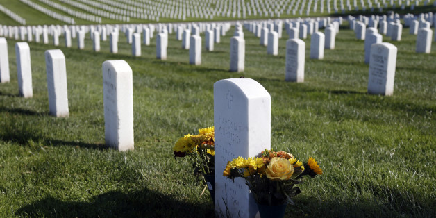Flowers are placed over a war veteran's tombstone at Golden Gate National Cemetery on Monday, Nov. 10, 2014, in San Bruno, Calif. The U.S. celebrates Veterans Day Tuesday in honor of those who have served in the nation's military. (AP Photo/Marcio Jose Sanchez)