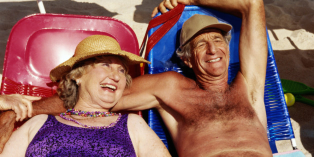 Senior couple lying on sun beds on beach, smiling