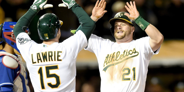 OAKLAND, CA - APRIL 06:  Stephen Vogt #21 of the Oakland Athletics is congratulated by Brett Lawrie #15 after Vogt hit a three-run homer against the Texas Rangers in the bottom of the seventh inning on Opening Day at O.co Coliseum on April 6, 2015 in Oakland, California.  (Photo by Thearon W. Henderson/Getty Images)