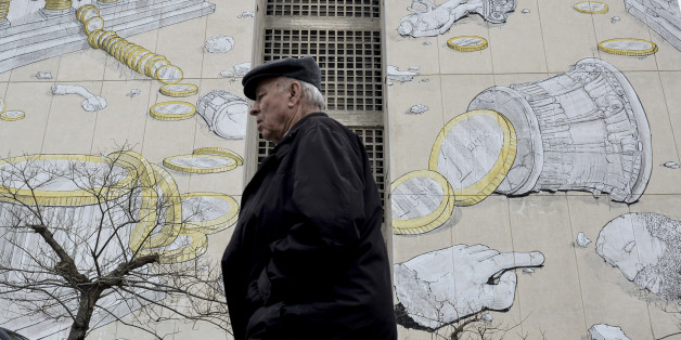 A man walks past a mural in the northern Greek town of Thessaloniki, on Wednesday, March 11, 2015. Greece is quickly running out of cash and has to repay debts this month to the International Monetary Fund — which co-funded Greece's 240 billion euro bailout — as well having as treasury bills coming due. (AP Photo/Giannis Papanikos)