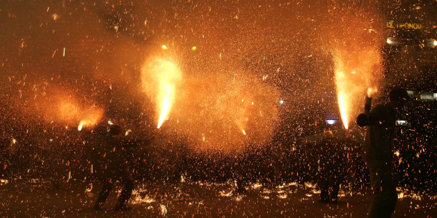 Revelers hold flares during pre-Easter celebrations in the city of Agrinio, western Greece, late Good Friday, April 25, 2008. The celebration, known as 'saitopolemos' in Greek, dates back to Greece's 1821-32 war of independence against the Ottoman Empire. (AP Photo/Petros Giannakouris)