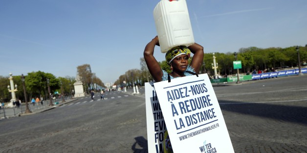 Gambian woman Siabatou Sanneh displays a sandwich board which translates as 'Help us to reduce the distance' as she carries a jerrycan of water on her head while walking the route of the 39th Paris Marathon in Paris, on April 12, 2015, to raise awareness for the cause of charity 'Water for Africa'.    Siabatou Sanneh's symbolic participation in the 39th Paris Marathon while carrying a jerrycan of water on her head was to raise awarness of the plight of many people living in Africa who must walk
