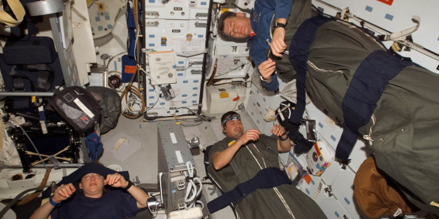 In this image provided by NASA, astronauts Pam Melroy, George Zamka, bottom right,and European Space Agency's Paolo Nespoli, sleep in their sleeping bags, which are secured on the middeck of the Space Shuttle Discovery while docked with the International Space Station, Thursday, Nov. 1, 2007.   (AP Photo/NASA)