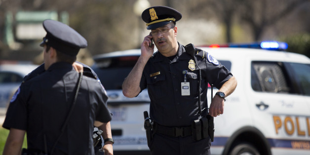 WASHINGTON, DC - APRIL 11:A U.S. Capitol Police officer talks on his phone near the west front of the U.S. Capitol on Capitol Hill, April 11, 2015 in Washington, DC.  According to the U.S. Capitol Police, the Capitol was on lockdown after shots were fired and a suspicious package was investigated. According to the U.S. Capitol Police, a person suffered a self-inflicted gunshot wound. (Photo by Drew Angerer/Getty Images)