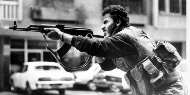 FILE - In this Feb. 20, 1987, file photo, a Shiite Muslim AMAL militiaman fires his AK-47 assault rifle during skirmishes with Druse irregulars on Corniche Mazraa road, West Beirut, Lebanon. The Lebanese civil war itself played out in several stages between 1975 and 1990. Over that time, Christians fought Palestinians, Lebanese Sunni and Shiite Muslims and Druse. At one point, Christian groups turned their guns on each other, in a nasty episode of fratricidal bloodshed later repeated by Shiite m