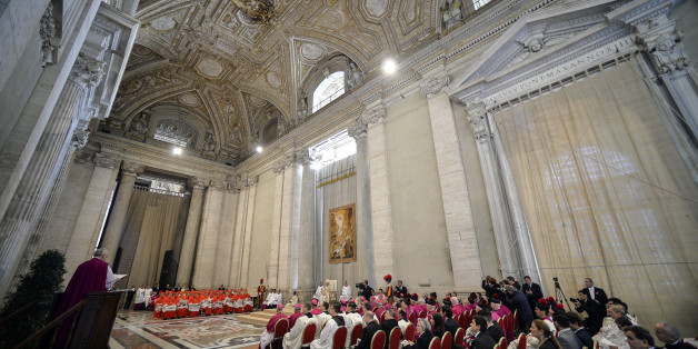"""Pope Francis, left, speaks in St. Peter's Basilica, at the Vatican, Saturday, April 11, 2015. Pope Francis has proclaimed a special year of efforts by the Catholic Church to be more merciful and less judgmental. At St. Peter's Basilica Saturday evening, he listened as a Vatican prelate read excerpts from a papal bull, or decree, in which Francis proclaimed an """"Extraordinary Jubilee of Mercy"""" Holy Year. The year begins on Dec. 8 with Francis' opening the normally closed Holy Door in the back of t"""