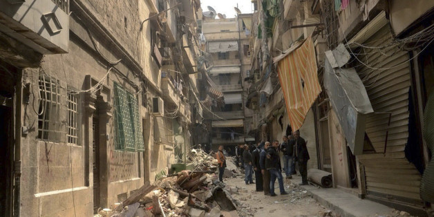 In this photo released by the Syrian official news agency SANA, Syrians gather in a street that was hit by shelling, in  the predominantly Christian and Armenian neighborhood of Suleimaniyeh, Aleppo, Syria, Saturday, April 11, 2015. Syrian state television and an activist group say opposition fighters have shelled the government-held neighborhood in the northern city of Aleppo, killing several people and wounding dozens. (AP Photo/SANA)