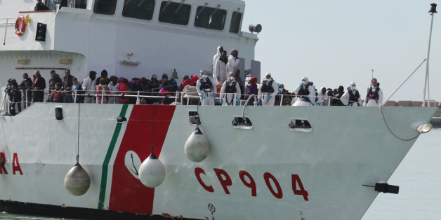 FILE - In this Wednesday, March 4, 2015, file photo, rescued migrants wait to disembark from an Italian Coast Guard vessel in Porto Empedocle, Sicily, southern Italy. In a dramatic sea rescue north of Libya, a flotilla of rescue ships saved nearly 1,000 migrants and refugees, while 10 migrants perished in the southern Mediterranean. European Union countries are immersed in a full-fledged migration crisis. With the EU lacking funds and resources, some officials are even floating the idea of a multinational border guard to deal with arrivals of hundreds of thousands from war-torn countries like Syria, poor African nations and non EU neighbors like Kosovo. (AP Photo/Francesco Malavolta, File)