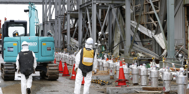 Workers wearing protective gears stand outside the Unit 4 reactor at the Fukushima Dai-ichi nuclear power plant in Okuma, Fukushima prefecture, northeastern Japan, Wednesday, Nov. 12, 2014. More than three years into Japan's massive cleanup of the tsunami-damaged nuclear plant, only a tiny fraction of the workers are focused on the key tasks of dismantling the broken reactors and removing radioactive fuel rods. (AP Photo/Shizuo Kambayashi, Pool)