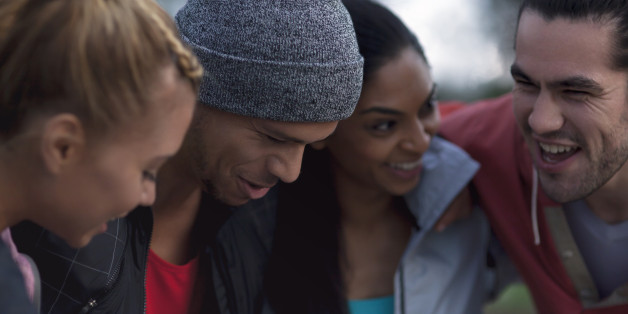 portrait of happy urban runners together at dusk, looking away from camera, landscape composition, two men aged 25 to 32, two women aged 26 to 32, full length action shot, urban landscape