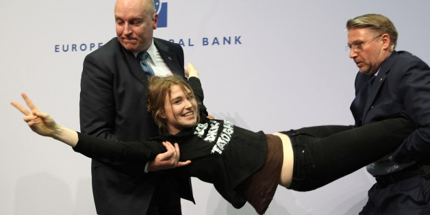 A woman is stopped by security after she interrupted a press conference by Mario Draghi, President of the European Central Bank (ECB) following a meeting of the Governing Council in Frankfurt / Main, Germany, on April 15, 2015. AFP PHOTO / DANIEL ROLAND        (Photo credit should read DANIEL ROLAND/AFP/Getty Images)