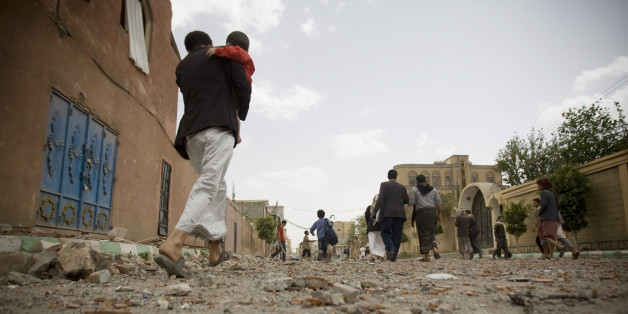 FILE - In this Wednesday, April 8, 2015 file photo, people flee after a Saudi-led airstrike in Sanaa, Yemen. A state-run broadcaster in Iran is reporting that the Islamic Republic has sent a navy destroyer and another vessel to waters near Yemen amid a Saudi-led airstrike campaign. (AP Photo/Hani Mohammed, File)