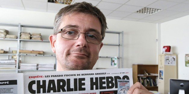 """FILE - In this Sept.19, 2012 file photo, Stephane Charbonnier also known as Charb , the publishing director of the satyric weekly Charlie Hebdo, displays the front page of the newspaper as he poses for photographers in Paris. The late former editor of French weekly Charlie Hebdo takes on politicians, the media and """"Islamophobia"""" as thinly veiled racism in a posthumously published book that was completed two days before he died in France's worst terror attack in years. (AP Photo/Michel Euler, Fil"""