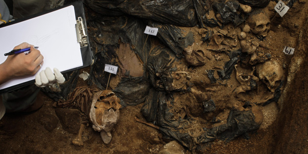A forensic takes notes at a mass grave found during renovation works at a public school in Mixco, in the outskirts of Guatemala City, Tuesday, Sept. 1, 2009. Investigators say that the skeletons of around 160 corpses found in the grave were moved from the local cemetery because of lack of space. A human rights group that gathers relatives of missing people said that the corpses could be of people who disappeared during Guatemala's internal conflict and asked for an investigations. (AP Photo/Rodrigo Abd)