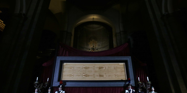 The Holy Shroud, the 14 foot-long linen revered by some as the burial cloth of Jesus, is on display at the Cathedral of Turin, Italy, Saturday, April 18, 2015. The long linen with the faded image of a bearded man, that is the object of centuries-old fascination and wonderment, will be on display for the public from April 19 to June 24, 2015. Pope Francis said he is planning to visit the Holy Shroud during a a pilgrimage to Turin next June 21, 2015. (AP Photo/Antonio Calanni)