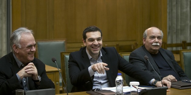 Greek Prime Minister Alexis Tsipras, center, jokes with ministers next to Deputy Prime Minister Giannis Dragasakis, left, and Minister of Interior and Administrative Reconstruction Nikos Voutsis during a cabinet meeting in Athens, on Sunday, March 29, 2015. (AP Photo/Petros Giannakouris)