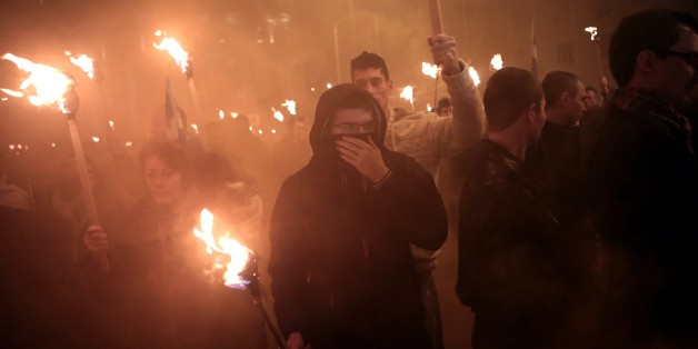 Members of the Greek ultra nationalist party Golden Dawn hold torches on January 31, 2015 during a gathering of Greek nationalists in central Athens, to commemorate the death of three Greek military officers. The crew of a Greek army helicopter crashed on January 31 at open sea in the Imia islets, at the Greek-Turkish sea borders, during a military crisis and subsequent dispute between the two countries over sovereignty of the islets in 1996. AFP PHOTO / ANGELOS TZORTZINIS        (Photo credit s