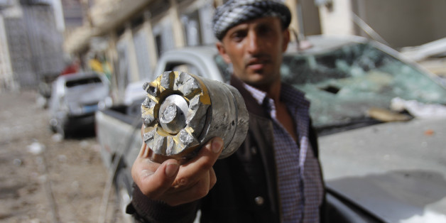 A man holds a projectile fragment after a Saudi-led airstrike against Iran-allied Shiite rebels, known as Houthis, hit a site of a weapons cache in Yemen's capital, Monday, April 20, 2015. Airstrikes on weapons caches in Yemen's rebel-held capital on Monday caused massive explosions that shattered windows, sent residents scrambling for shelter and killed a local TV presenter. (AP Photo/Hani Mohammed)