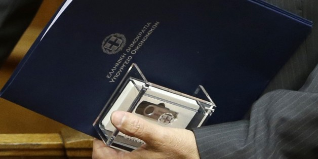 Greece's Finance Minister Gikas Hardouvelis, holds a clear case with two flash drives containing the new state budget for 2015 at the Greek parliament in Athens, on Friday, Nov. 21, 2014. Greece's government has submitted its 2015 budget to Parliament, predicting the debt-ridden country's economy will emerge from recession with growth of 2.9 percent and a primary surplus _ income without taking into account interest payments on outstanding debt _ of 3 percent of gross domestic product. The blue envelop reads ''Hellenic Republic, Finance Ministry.'' (AP Photo/Thanassis Stavrakis)