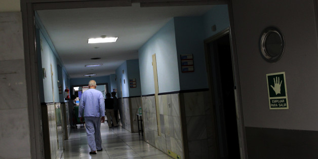 """A reading """"Hospital unit, beds 3201 to 3240"""" are seen, as a patient walks down a corridor in a Hospital in Madrid, Spain, Monday, March 25, 2013. The European financial crisis has not only sent stock markets plummeting and driven protesters to the street, but it is also being blamed for health problems across the continent including a spike in suicides and disease outbreaks, according to new research. Since the crisis first struck in 2008, the hardest-hit countries have sharply curtailed their h"""