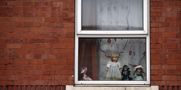Dolls are displayed in an upper floor window of a house in the Eastwood area of Rotherham, South Yorkshire, North England, on October 6, 2014.  An inquiry revealed on August 26, 2014 that  some 1,400 minors were sexually abused in the British town of Rotherham over a 16-year period and blamed local authorities for failing to act. The inquiry followed the conviction of five men in 2010 for sexual offences in Rotherham at a trial in which they were found guilty of grooming teenage girls for sex. AFP PHOTO / OLI SCARFF        (Photo credit should read OLI SCARFF/AFP/Getty Images)