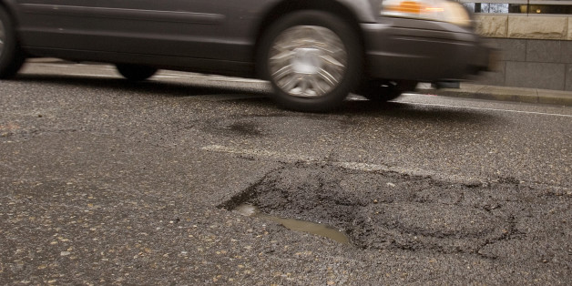 Downtown traffic passes a pothole in Portland, Ore., Thursday, Feb 11, 2010.  If you live in Portland and spot a nasty pothole, burned-out streetlight or noxious graffiti, Mayor Sam Adams wants you to grab your iPhone and report it.(AP Photo/Don Ryan)
