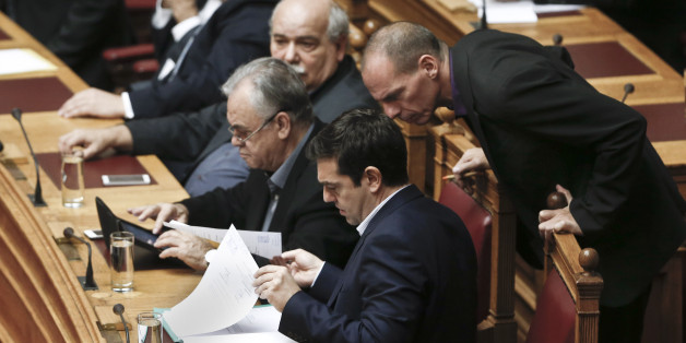 Greek Minister Alexis Tsipras front and his Finance Minister  Yanis Varoufakis, right, look on papers during the vote for the president of Greece's parliament in Athens, on Friday, Feb. 6, 2015. Barely 10 days after radical left-wing Syriza was swept to power in Athens, analysts expect a compromise over Greece's debts to emerge, allowing it to remain a member of the 19-country eurozone. The finance ministers of the 19-country eurozone are to meet at a special meeting Wednesday on the eve of a summit of European Union leaders to discuss Greece's debts. (AP Photo/Petros Giannakouris )