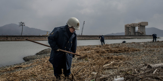 RIKUZENTAKATA, JAPAN - MARCH 11:  A police officer searches the shoreline for the remains of tsunami victims or any identifying personal items on March 11, 2015 in Rikuzentakata, Japan. Police from Iwate prefecture continue to search for remains, and personal items that could be returned to loved ones on the 11th of every month. On March 11 Japan commemorates the fourth anniversary of the magnitude 9.0 earthquake and tsunami that claimed more than 18,000 lives, and subsequent nuclear disaster at the Fukushima Daiichi Nuclear Power Plant.  (Photo by Chris McGrath/Getty Images)