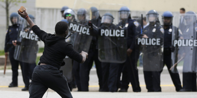 A man throws a brick at police Monday, April 27, 2015, following the funeral of Freddie Gray in Baltimore. (AP Photo/Patrick Semansky)